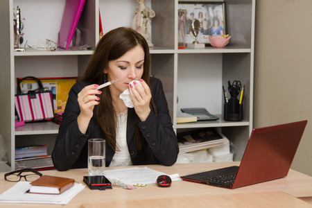sick leave: Cute business woman in the office at the computer Stock Photo