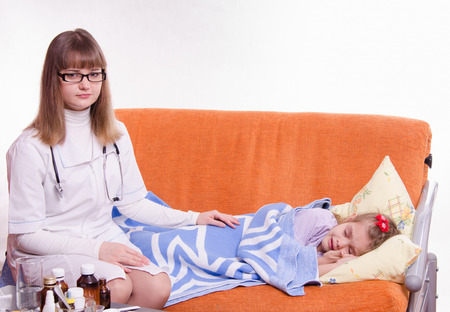 house robes: Doctor pediatrician examines a sick child at home Stock Photo