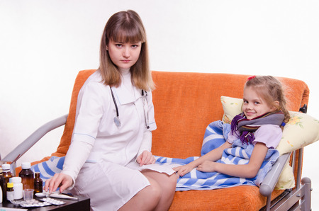measures white house: Doctor pediatrician examines a sick child at home Stock Photo