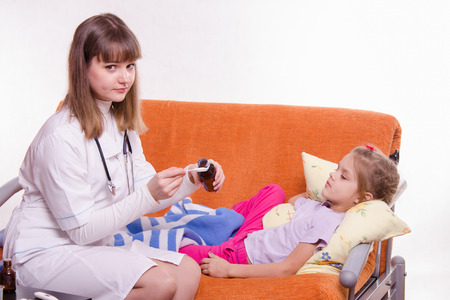house robe: Doctor pediatrician examines a sick child at home Stock Photo