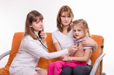 Doctor pediatrician examines a sick child at home in the presence of my mother