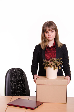 kicked out: Woman fired from her job at the office, looking sadly into the frame with a box and a potted flower in hand Stock Photo