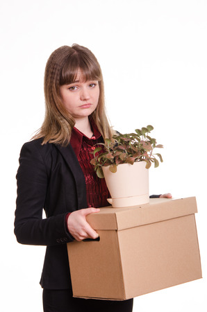 kicked out: Sad girl fired from her job and holding a box with things