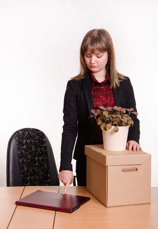 kicked out: Woman fired from her job at the office, looking sadly at the table, closes the laptop, standing next to a box with things and flower room