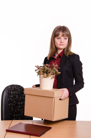 demotion: Woman fired from her job at the office sad looks away with a box and a potted flower in hand