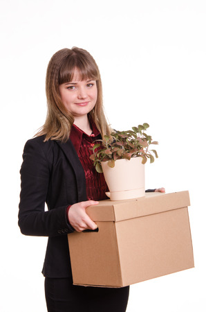 careerist: Smiling girl adopted at work in the office holding a box with things and flower room Stock Photo