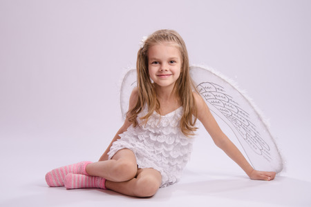 six year old: Six year old girl in a bright angel costume with wings on a white background Stock Photo