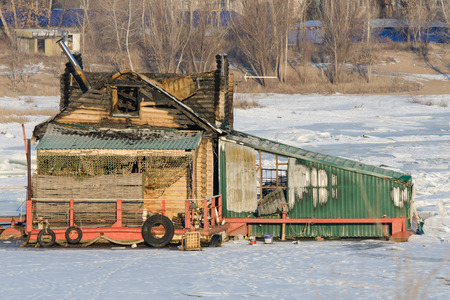conflagration: Burnt wooden structure standing on the frozen river Stock Photo