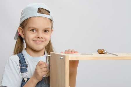 allen key: Little girl - collector of furniture with an Allen key is trying to screw a screw into the wooden frame of the chest