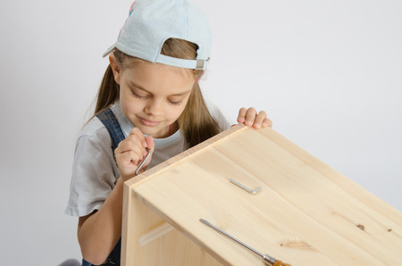 baby wardrobe: Little girl - collector of furniture twists the screw on the wooden frame of the chest