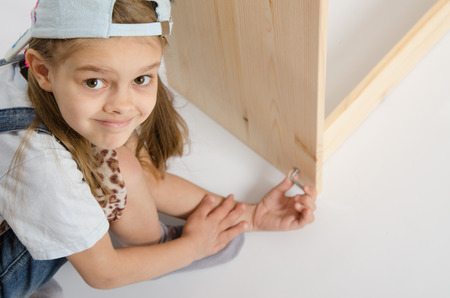 baby wardrobe: Little girl - collector of furniture twists the screw on the dresser