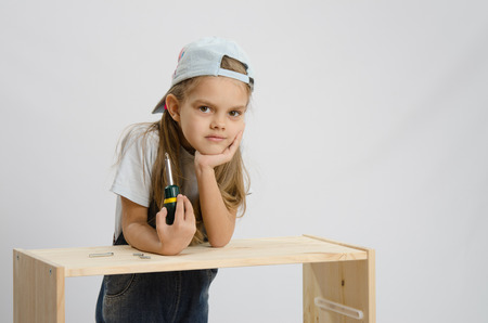 leaned: Little girl - collector of furniture with a screwdriver in his hand thoughtfully leaned on unfinished furniture and laid her head on her hand Stock Photo