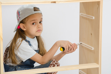 baby wardrobe: Little girl - collector of furniture with a screwdriver in his hand collects wooden cabinet Stock Photo