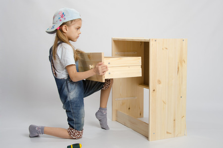 wooden insert: Little girl - furniture collector tries to insert a box in a wooden chest of drawers Stock Photo