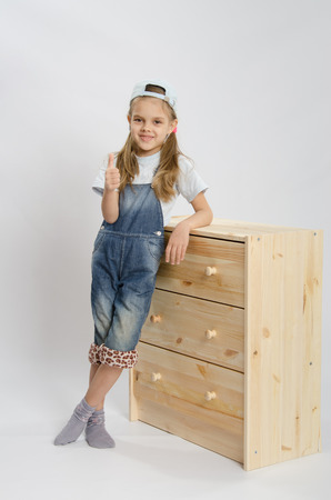 Little girl - collector of furniture in overalls relies on a chest of drawers and shows class photo