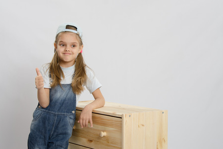 baby wardrobe: Little girl - collector of furniture in overalls relies on a chest of drawers and shows class Stock Photo