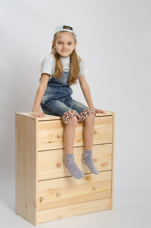 relies: Little girl - collector of furniture in overalls relies on a chest of drawers and shows class Stock Photo