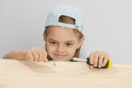 euro screw: Six year old girl playing and collecting wooden cabinet Stock Photo