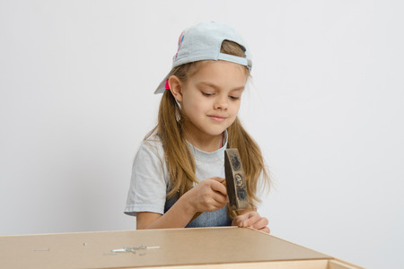 Six year old girl playing and collecting wooden cabinet photo