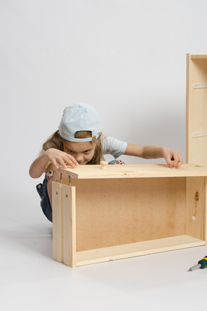 six year old: Six year old girl playing and collecting wooden cabinet Stock Photo