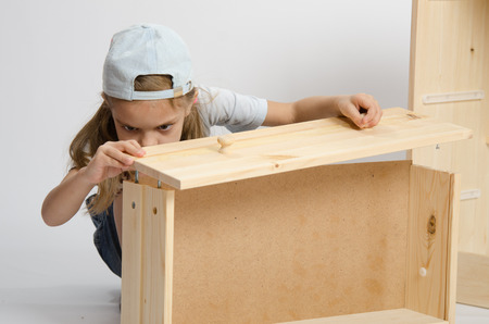 Six year old girl playing and collecting wooden cabinet Foto de archivo