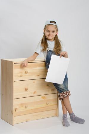 Zes jaar oud meisje spelen en verzamelen van houten kast Stockfoto