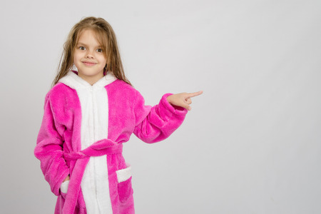 a bathing place: Six year old girl with wet hair in a bathrobe on a light background Stock Photo