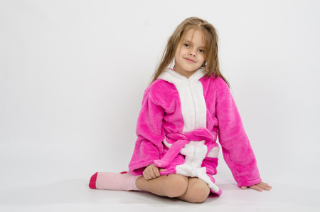 six girl: Six year old girl with wet hair in a bathrobe on a light background Stock Photo