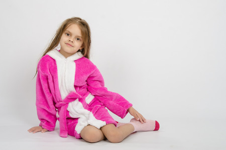 six year old: Six year old girl with wet hair in a bathrobe on a light background Stock Photo