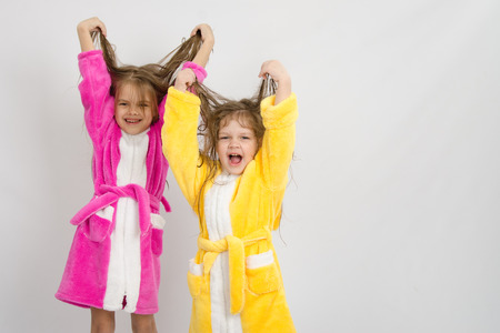 bath robes: Two sister girls with wet hair standing in the bath robes on a light background