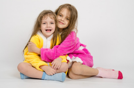 bath robes: Two sister girls sitting in the bath robes on a white background Stock Photo