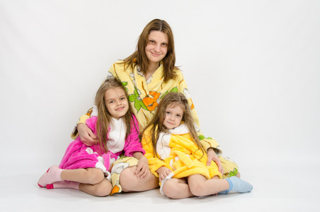 bath robes: Mom with two daughters sitting in the bath robes on a white background