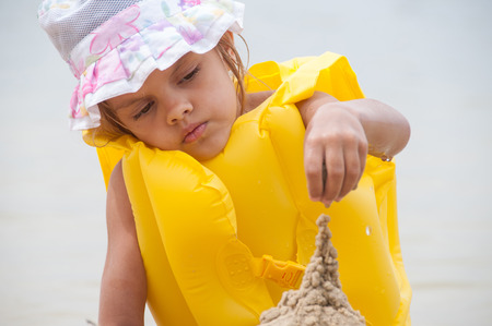 lifejacket: Five-year girl in a lifejacket is building a sand castle Stock Photo