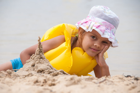 five year: Five year old girl on the beach sand built tower