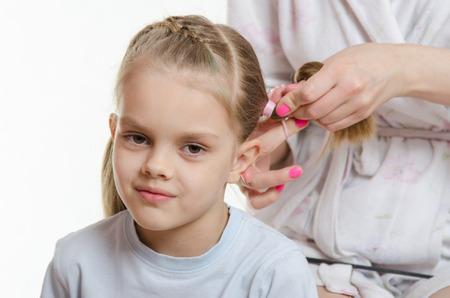 six year old: Mom braids long hair elastics cute six year old daughter Stock Photo
