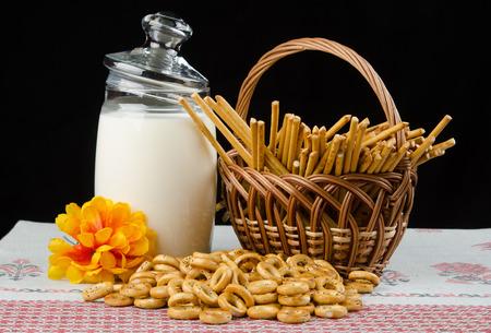 milkman: Still life on a black background. Milkman, a basket of sticks, drying Stock Photo