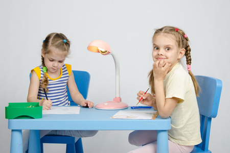 six years: Two girls of four and six years of sitting at the table and draws and paints and pencils Stock Photo