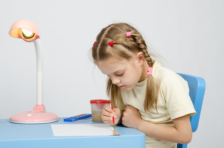 six year old: Six year old girl Europeans draws paints on a sheet of sitting at the table