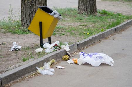 쓰레기는 도시 거리의 쓰레기통 주위에 흩어져 있습니다. 스톡 콘텐츠 - 40163371