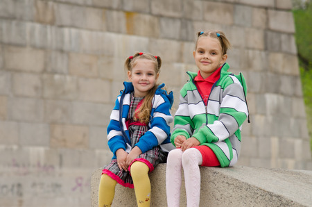 six years: two girls of four and six years of walking on the embankment of the river