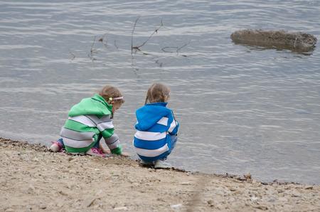 enthusiastically: Two children enthusiastically walk along the river bank Stock Photo