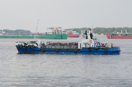 floats: A small boat floats past standing in the roads tankers