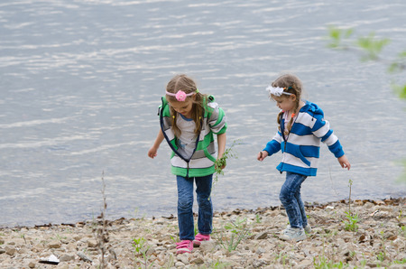 enthusiastically: Two children enthusiastically walk along the river bank, and something to look for and collect