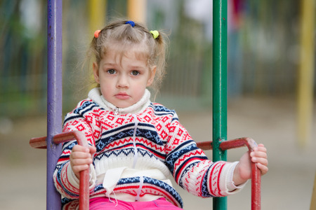 sweater girl: On the playground in cool weather upset four-year girl riding on a swing Stock Photo