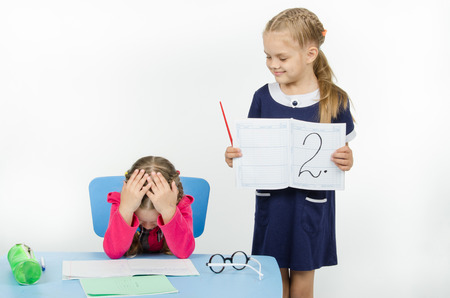 unsatisfactory: Two girls play school teacher and student Stock Photo