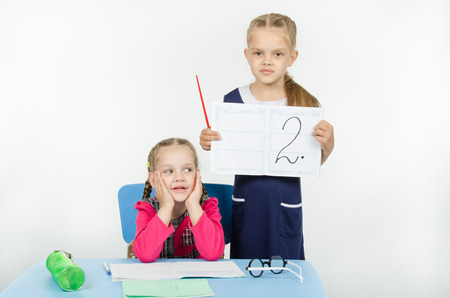 poorly: Two girls play school teacher and student Stock Photo