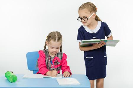 dictating: Dos ni�as juegan maestro de escuela y estudiante
