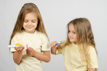 six years: Two girls of four and six years of brushing their teeth toothbrushes
