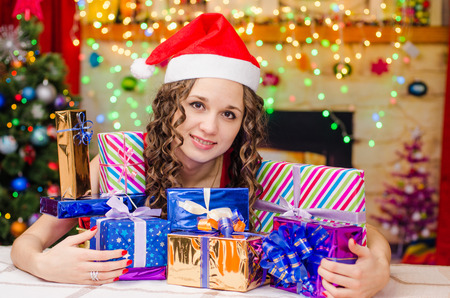 christmas atmosphere: Young beautiful girl sitting at a table with Christmas gifts in the Christmas atmosphere Stock Photo