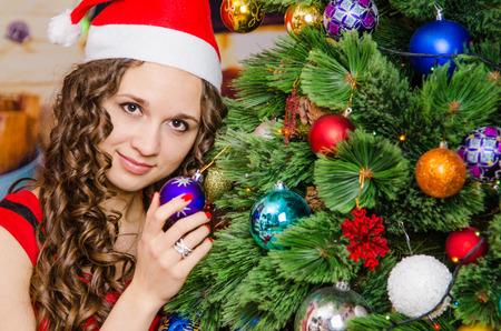 decorates: Young beautiful girl decorates Christmas tree toys Stock Photo